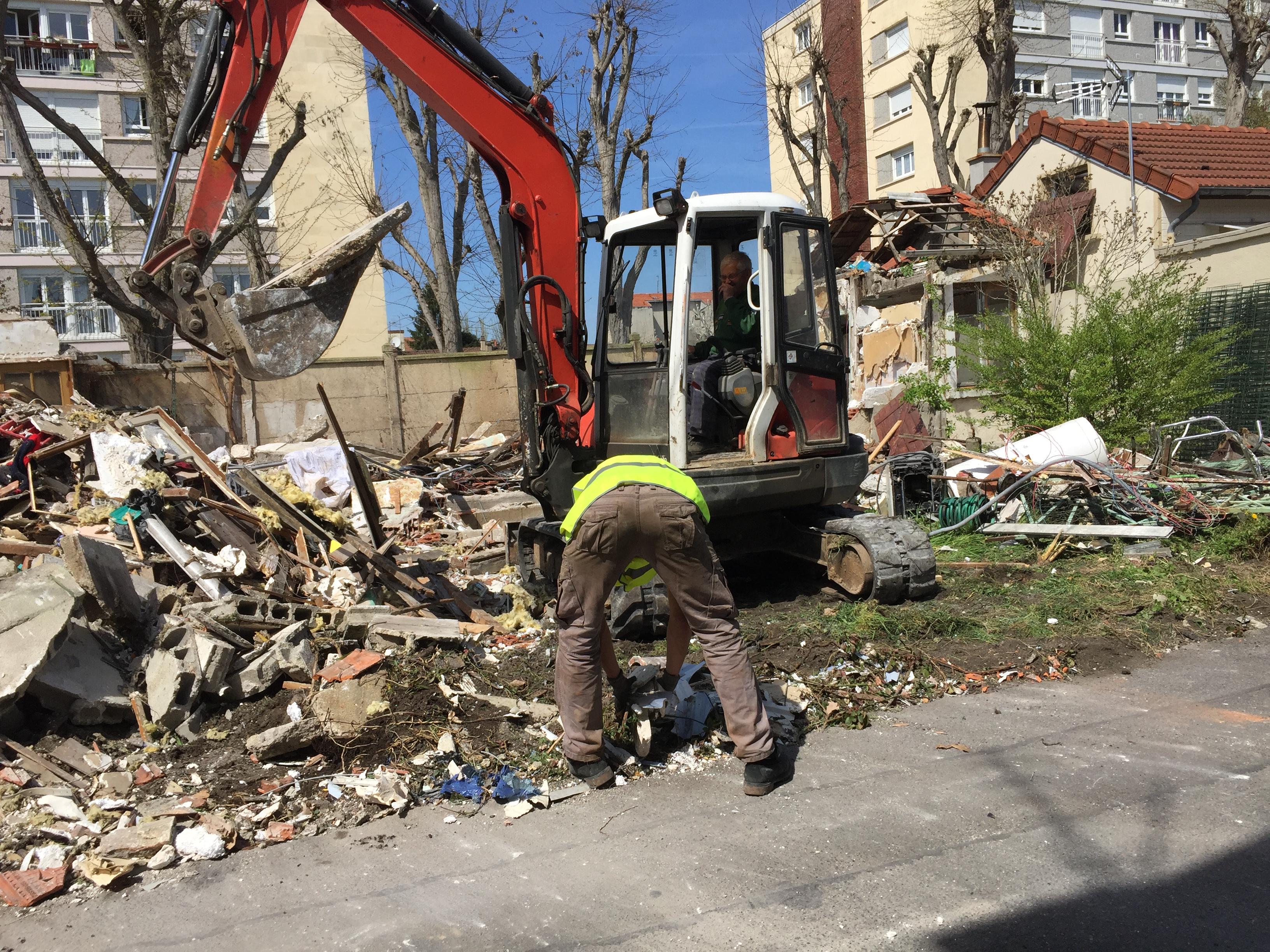 Ouvrier avec pelleteuse sur chantier de démolition